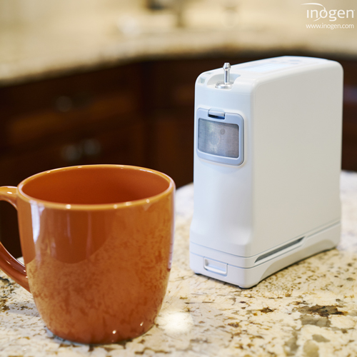 Inogen One G4 next to a coffee cup