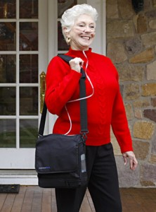 oxygen therapy, o2 therapy. Older Woman with nasal cannula, carrying portable oxygen, smiling outside.