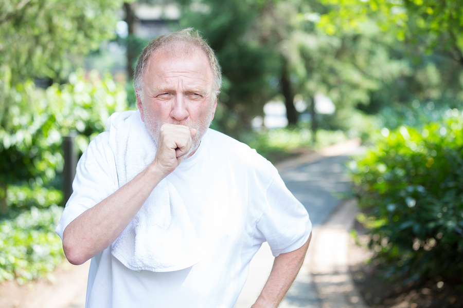 man coughing while walking on a trail