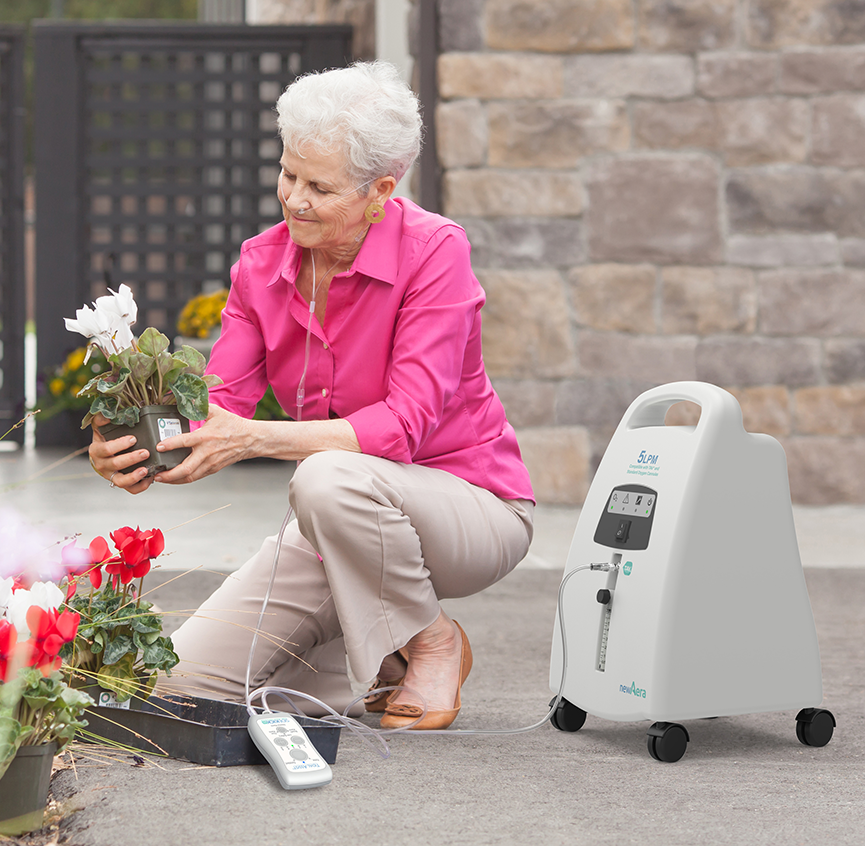 Woman planting flowers with Inogen TAV and Nidex 5 Stationary Oxygen Concentrator