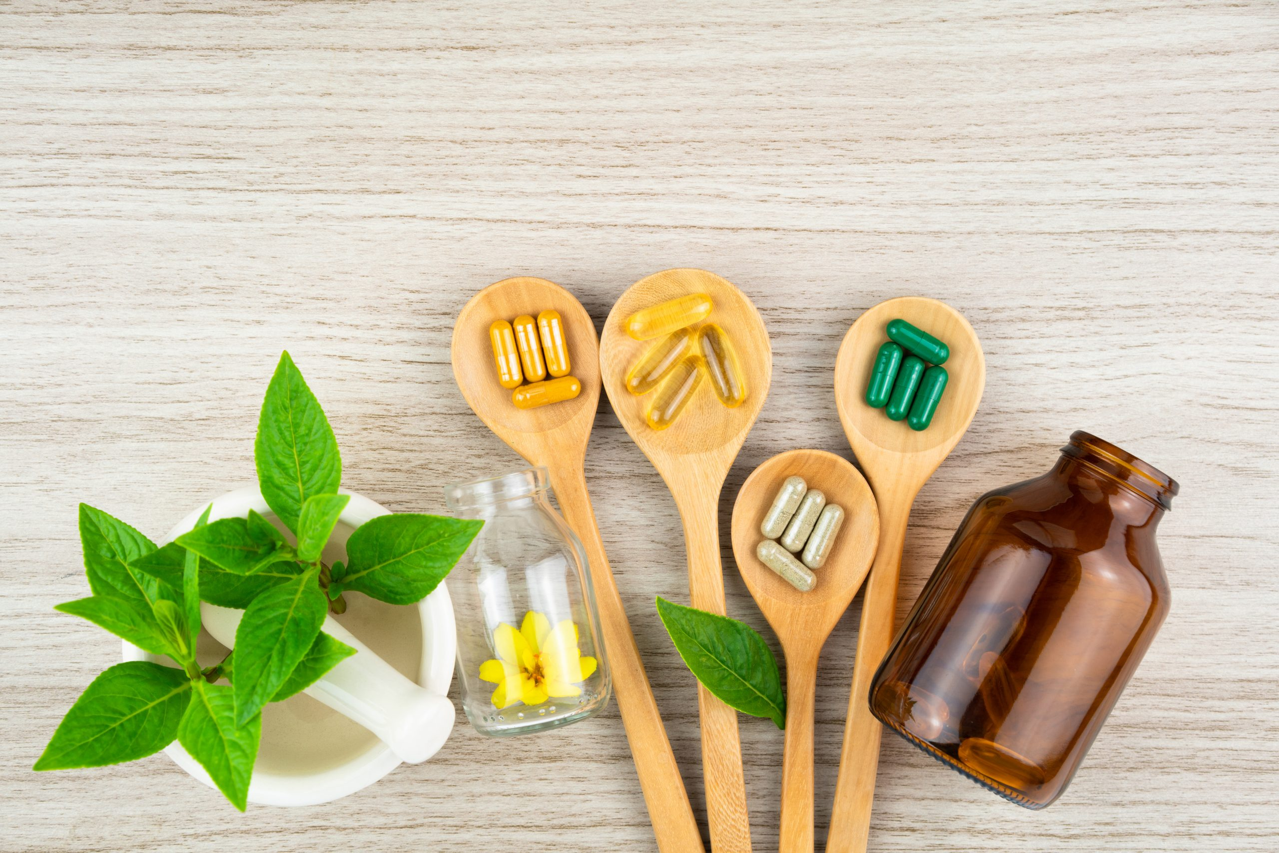 Wooden spoon holding dietary supplements