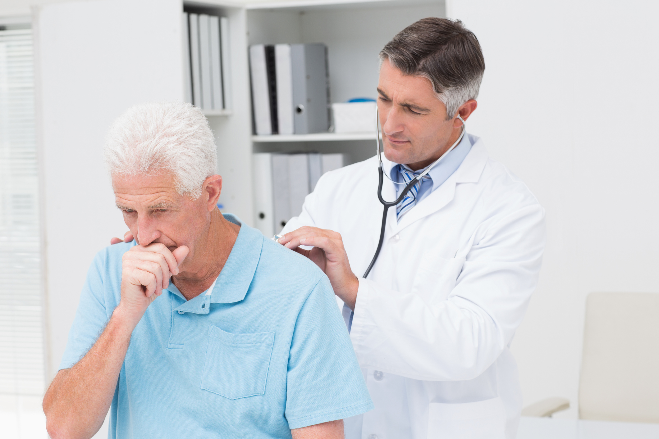 Doctor listening to patient's lungs as the patient coughs