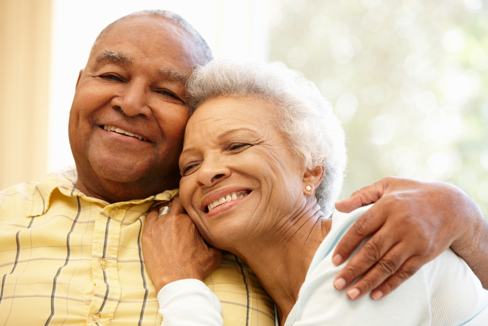 older couple smiling together with woman resting head on man