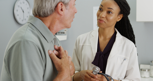 Woman Doctor consulting patient and patent has hands over his chest
